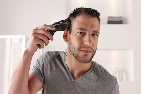Homme qui se coupe les cheveux soit même avec une tondeuse électrique